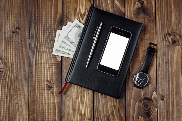 Vista superior del teléfono inteligente, reloj, bolígrafo, cuaderno y dinero