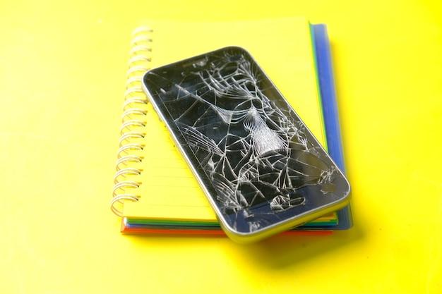 Vista superior del teléfono inteligente roto en superficie amarilla