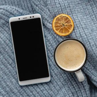 Vista superior del teléfono inteligente en suéter con taza de café y cítricos secos