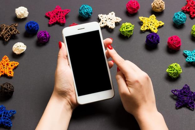 Vista superior del teléfono en mano femenina. decoraciones de navidad. vacaciones de año nuevo.