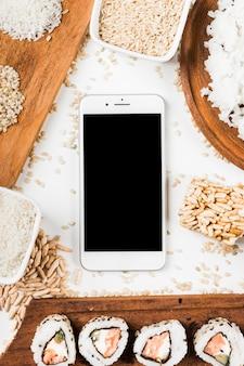 Vista superior del teléfono móvil rodeado de sushi y variedad de arroz crudo.