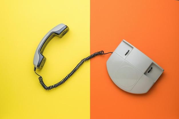 Vista superior de un teléfono retro con el auricular apagado sobre un fondo amarillo y naranja. endecha plana.