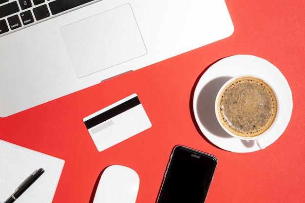 Vista superior del teléfono con tarjeta de crédito y taza de café