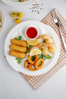 Vista superior de tempura de calamares y camarones y palitos de queso frito en un plato blanco