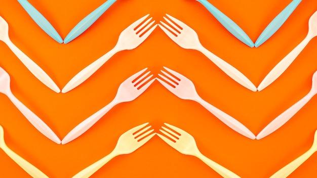 Vista superior del tenedor de plástico sobre fondo naranja