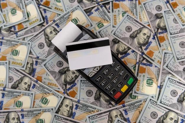Vista superior de la terminal con tarjeta de crédito en billetes de dólar