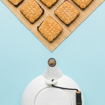 Vista superior tetera y galletas sobre la mesa