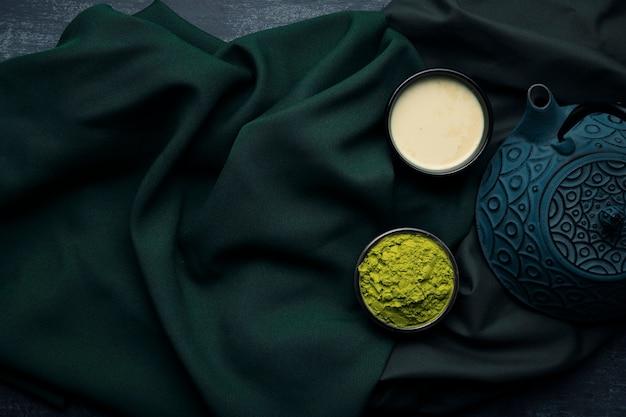 Vista superior tetera sobre tela con taza de té asiático matcha