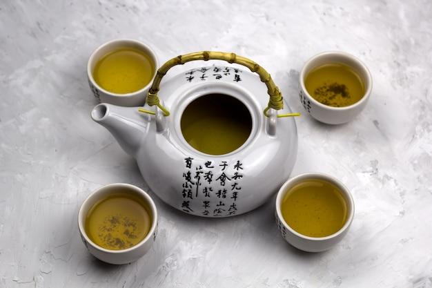 Vista superior de teteras y tazones de té con fondo de hormigón de jeroglíficos