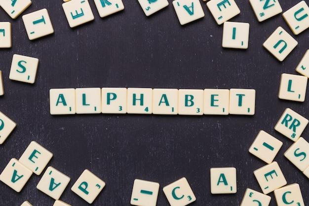 Vista superior del texto del alfabeto con letras scrabble sobre fondo negro