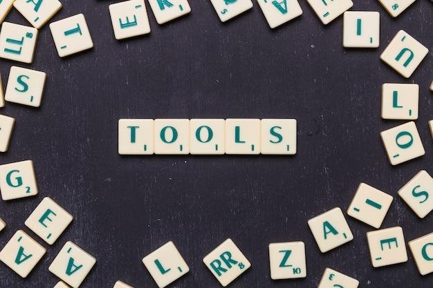Vista superior del texto de herramientas en letras de scrabble sobre fondo negro