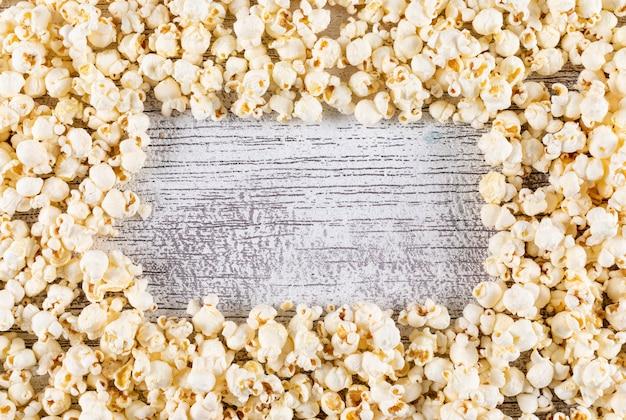 Vista superior de la textura de palomitas de maíz con espacio de copia en el centro en madera blanca horizontal