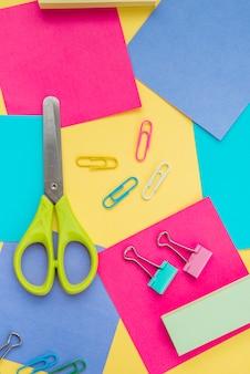 Vista superior de tijera; clip y nota adhesiva de colores