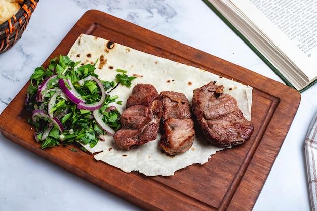 Vista superior tika kebab en pan de pita con hierbas y cebollas en una pizarra