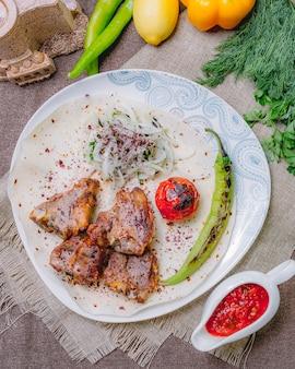 Vista superior de tika kebab en pan de pita con tomate y pimiento verde a la parrilla con hierbas y cebollas