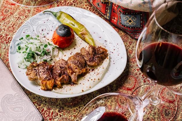 Vista superior tika kebab en pan de pita con verduras y cebollas a la parrilla y una copa de vino