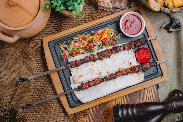 Vista superior tike kebab en brochetas de pan de pita con ensalada de verduras y salsa de tomate