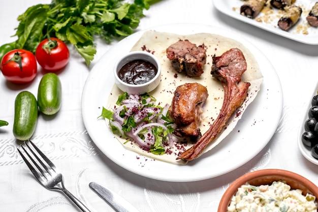 Vista superior tike kebab en pan de pita con hierbas y cebollas con salsa y verduras
