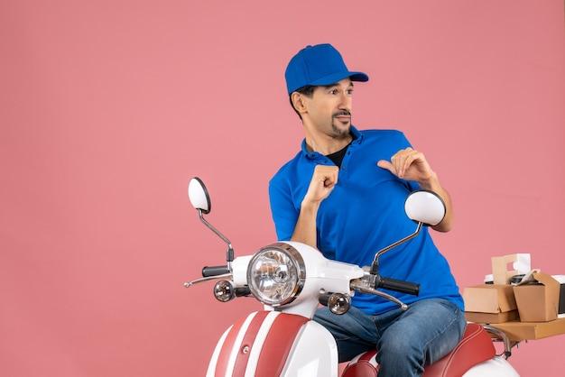 Vista superior del tipo de mensajero asustado con sombrero sentado en scooter entregando pedidos sobre fondo de melocotón pastel Foto gratis
