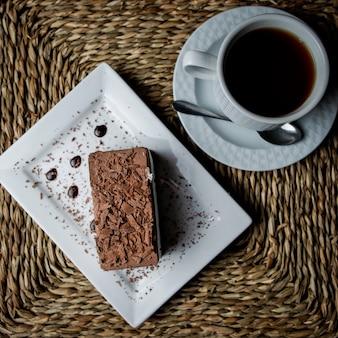 Vista superior de tiramisú de chocolate con una taza de té y un plato blanco y una cuchara en servilletas