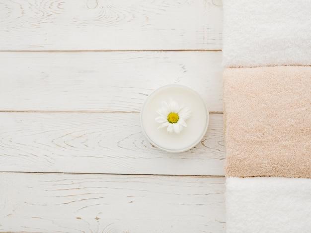 Vista superior de toallas y crema para spa.