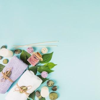 Vista superior de las toallas; piedras de spa; hojas; fregado botella y velas sobre fondo azul