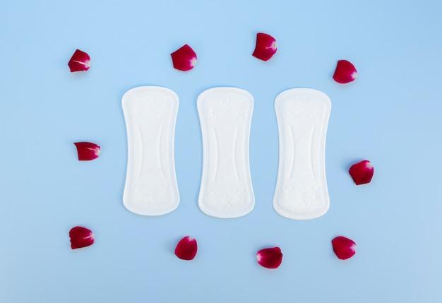 Vista superior de toallas sanitarias rodeadas de pétalos