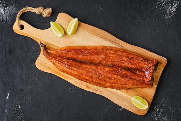 Vista superior de toda la anguila ahumada sobre tabla de cortar de madera