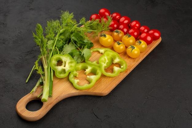 Vista superior tomates amarillos y rojos junto con pimiento verde en rodajas y hojas verdes en el piso oscuro