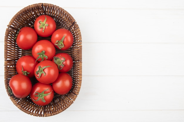 Vista superior de tomates en la canasta en el lado izquierdo y superficie blanca con espacio de copia