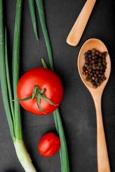 Vista superior de tomates con cebolletas y cuchara de madera con especias de pimienta sobre superficie negra
