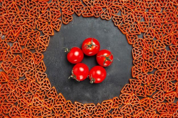 Vista superior de tomates cherry alrededor de pasta italiana corazón rojo