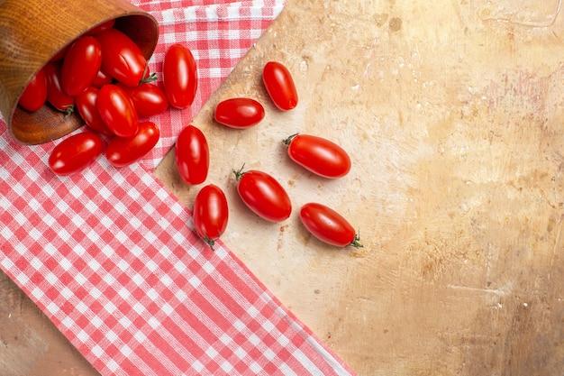 Vista superior de tomates cherry esparcidos del cuenco una toalla de cocina sobre fondo ámbar