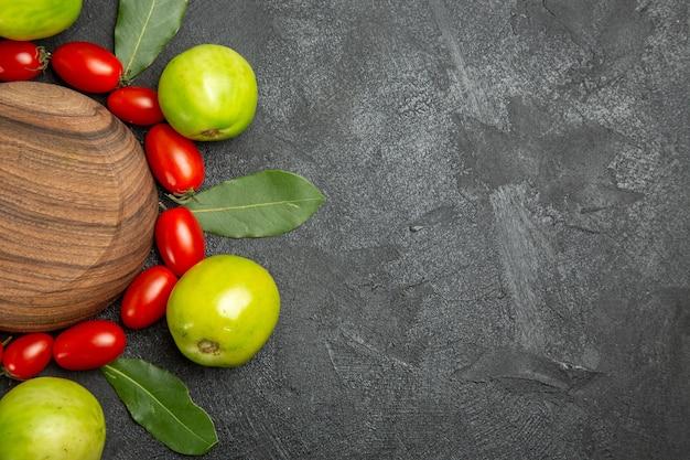 Vista superior de tomates cherry tomates verdes y hojas de laurel alrededor de una placa de madera sobre un suelo oscuro con espacio de copia