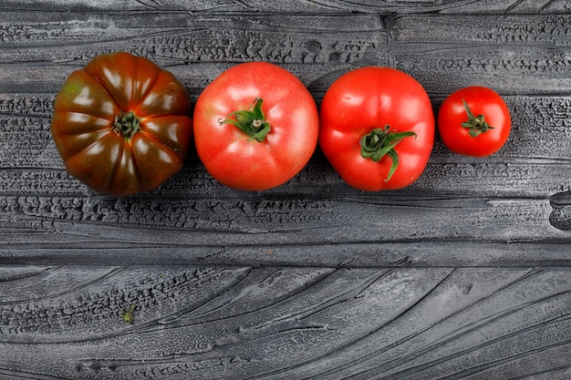 Vista superior de tomates coloridos en una pared de madera gris