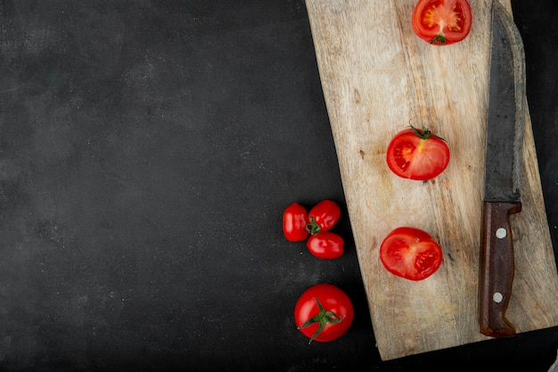 Vista superior de tomates frescos y mitades sobre tabla de cortar de madera junto a un cuchillo de cocina sobre fondo negro