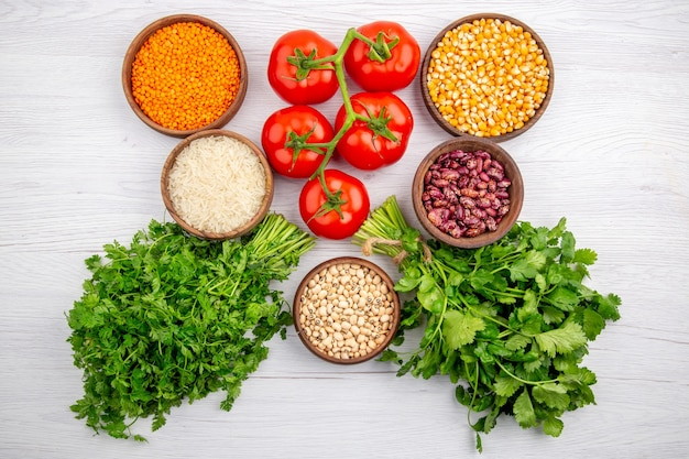 Vista superior de tomates frescos con tallo de maíz, lentejas amarillas, paquete de verduras, pimienta, arroz largo en mesa blanca
