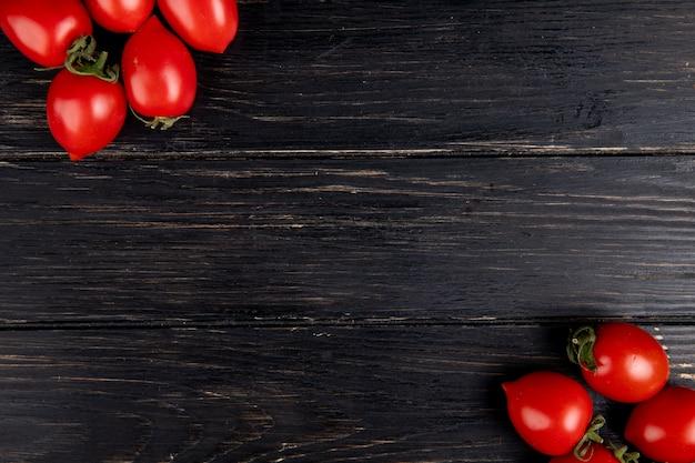 Vista superior de tomates en los lados izquierdo y derecho y madera con espacio de copia