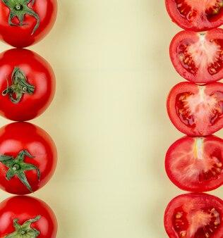 Vista superior de tomates en los lados izquierdo y derecho sobre una superficie amarilla con espacio de copia