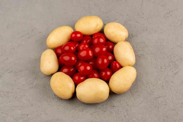 Vista superior tomates papas de forma redonda en el piso gris