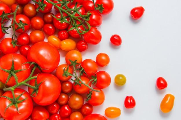 Vista superior de tomates pequeños y grandes sobre fondo blanco. horizontal