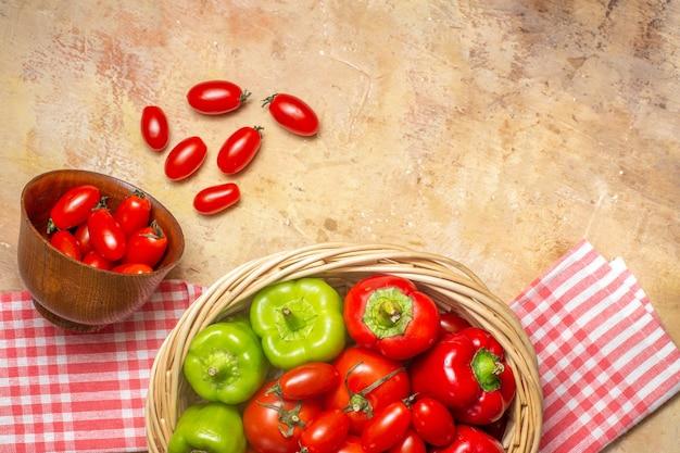 Vista superior de tomates pimientos verdes y rojos en una cesta de mimbre tomates cherry esparcidos de una toalla de cocina de tazón sobre fondo ámbar