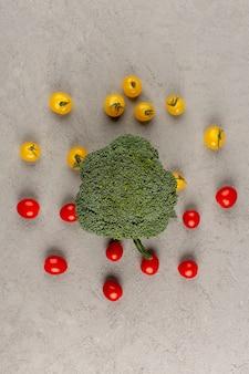 Vista superior de tomates rojos amarillos junto con brócoli verde sobre el fondo gris