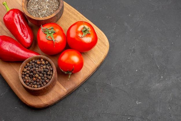 Vista superior de tomates rojos frescos con condimentos en el espacio oscuro