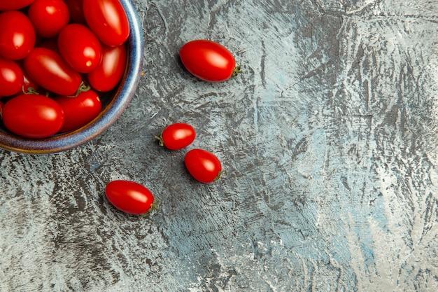 Vista superior de tomates rojos frescos dentro de la placa en la mesa de luz oscura foto de fruta oscura