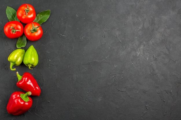 Vista superior de tomates rojos frescos con pimientos en ensalada de color de mesa oscura madura