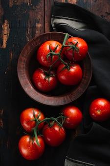 Vista superior de tomates rojos con tallo en un tazón
