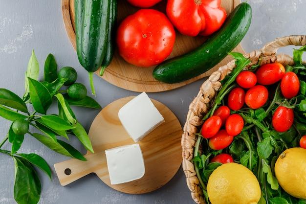Vista superior de tomates en tabla de cortar con limón, pepino, queso, verduras sobre superficie gris