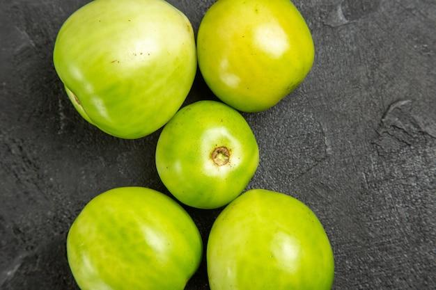Vista superior de tomates verdes en mesa oscura con espacio de copia