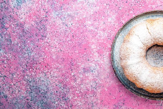Vista superior de la torta de azúcar en polvo redonda formada en el escritorio rosa